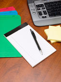 Close up image of pen and notepad with files on office desk — Stock Photo