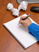 Close up shot of a person writing on spiral notepad on desk — Stockfoto