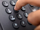 Close up shot of human finger pressing landline phone number — Foto Stock