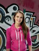Happy beautiful female against graffiti — Stock Photo