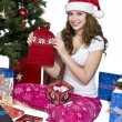 Smiling young woman showing her christmas gift — Stock Photo