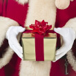 Santa holding gift - Stock Photo