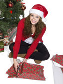 Blonde lady cutting the gift wrapper — Stock Photo