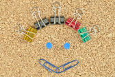Happy face made of colorful clips — Stock Photo