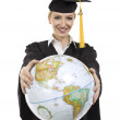 Female graduating student holding world globe — Stock Photo