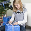 Stock Photo: Girl unpacking christmas present