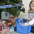 Stock Photo: Girl unwrapping her christmas gift by christmas tree
