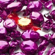 Golden hard candy arranged in between purple hard candies - Foto Stock