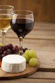 Cropped image of grapes with feta cheese and wine glasses — Stock Photo