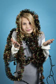 Girl gesturing with christmas lights and decorations — Stock Photo