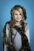 Girl smiling while wrapped in tinsel — Stock Photo