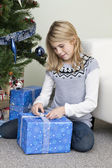 Girl unpacking a christmas present — Stock Photo