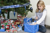 Girl unwrapping her christmas gift by the christmas tree — Stock Photo