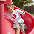 Happy boy sliding on red slide — Stock Photo