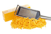 Grated bar of cheddar cheese and metal grater — Stock Photo