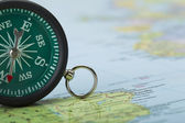 Green compass on the map — Stock Photo