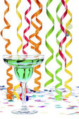 Green drink in glass with streamer and confetti in background — Stock Photo