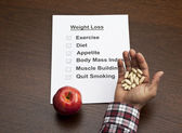Handful of capsules with apple and weight loss paper on table — Stock Photo