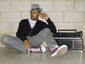 Attractive guy sitting on the floor with a boom box — Stock Photo