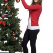 Attractive woman decorating christmas tree — Stock Photo #17160519