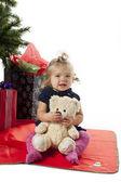 Menina sentada com urso de pelúcia com árvore de Natal e Cristo — Fotografia Stock