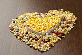 Beans in heart shape on wooden table — Stock Photo