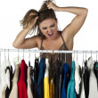 Frustrated woman trying to choose clothes — Stock fotografie