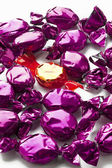 Golden hard candy arranged in between purple hard candies — Stock Photo