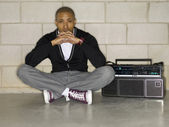 Good looking guy sitting on the floor with a boom box — Stockfoto