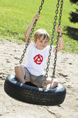 Happy elementary boy sitting on tyre swing — Stock Photo