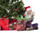 Happy elementary girl holding her christmas gift — Stockfoto