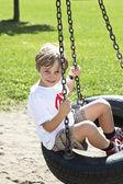 Happy little boy swinging on tire swing — Stock Photo