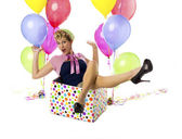 Happy young woman sitting in a box with balloon on the side — Stock Photo