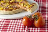 Hawaiian pizza and a whole ripe tomato — Stock Photo