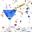 Martini glass with blue alcohol and yellow streamer — Stock Photo #17210155