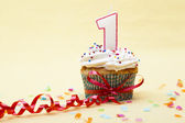 Number 1 candle on cupcake tied with streamer — Stock Photo
