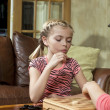 Girl playing checkers game - Stock Photo