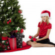 Girl with her christmas gift sitting beside christmas tree — Stock Photo