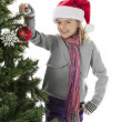 Girl holding christmas bauble with hand on hips — Stock Photo