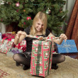 Stock Photo: Girl unwrapping gift
