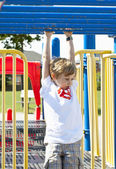 Elementary boy on monkey bars — Stock Photo