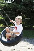 Elementary boy swinging on tire swing — Stock Photo