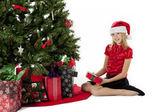 Girl with her christmas gift sitting beside christmas tree — Stock Photo