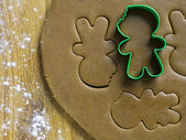 Gingerbread cookie cutter on dough — Stock Photo