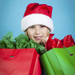Girl with santa hat holding shopping bags — ストック写真