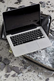 Laptop on broken television pieces — Stockfoto
