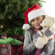 Portrait of a girl holding christmas teddy bear — Stock Photo