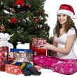 Portrait of a smiling young woman holding her christmas gift - Stock Photo