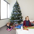 Portrait of brother and sister with christmas gift box in a livi — Stock Photo