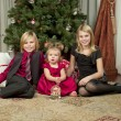 Portrait of brother and sisters sitting on floor with christmas — Stock Photo